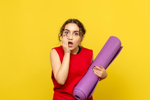 노란색 벽에 보라색 카펫을 들고 젊은 여자의 전면보기 무료 사진