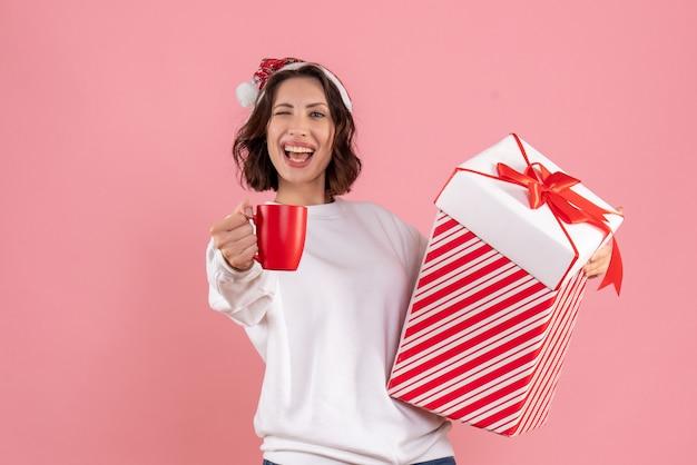 ピンクの壁にクリスマスプレゼントとお茶を保持している若い女性の正面図 無料写真
