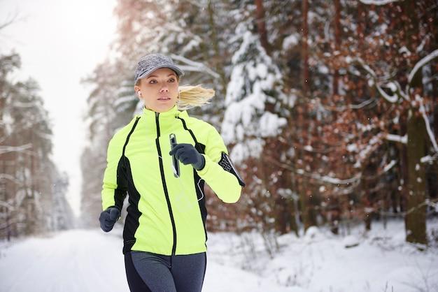 走って音楽を聴いている若い女性の正面図 無料写真