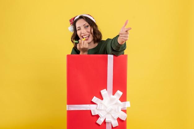 黄色の壁のボックス内に立っている若い女性の正面図 無料写真
