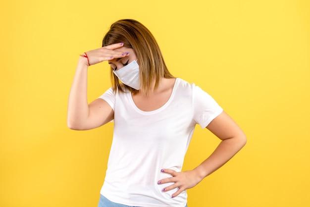 Вид спереди молодой женщины, подчеркнутой в маске на желтой стене Бесплатные Фотографии