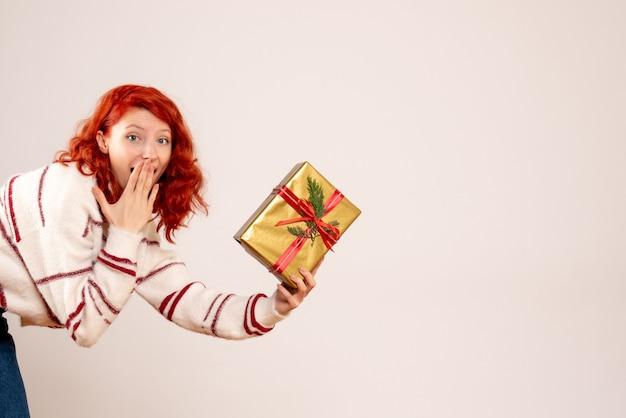 Вид спереди молодой женщины с рождественским подарком на белой стене Бесплатные Фотографии