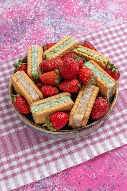 ピンクの壁に新鮮な赤いイチゴとおいしいワッフルクッキーの正面図 無料写真