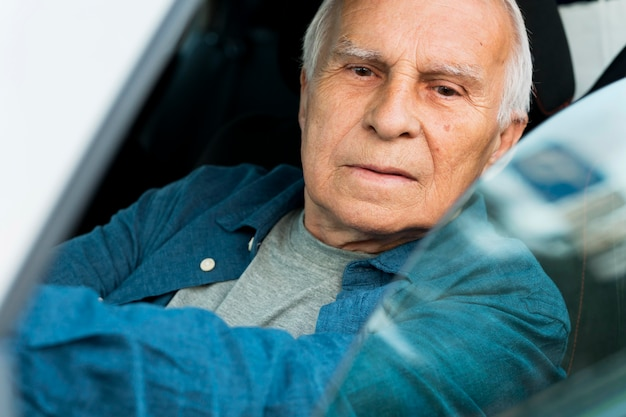 Front view of old man in personal car Free Photo