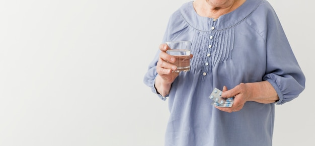 Front view of older woman taking her pills with copy space Free Photo