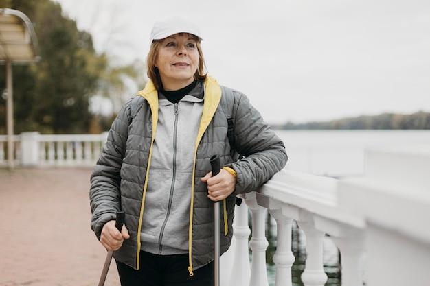 Vista frontale della donna anziana con bastoncini da trekking Foto Gratuite