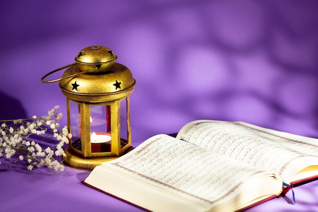 Front view open quran next to candleholder Free Photo