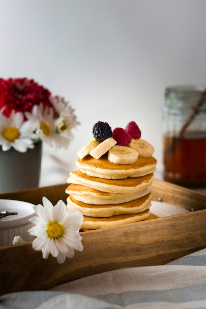Front view pancake tower with banana and raspberries Free Photo