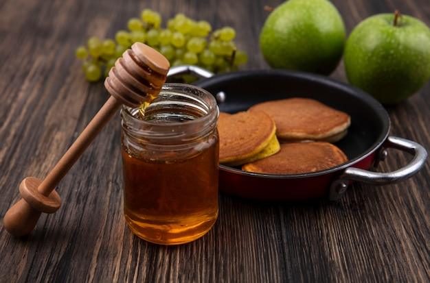 Вид спереди блины на сковороде с медом в банке с деревянной ложкой и зеленым виноградом с яблоками на деревянном фоне Бесплатные Фотографии