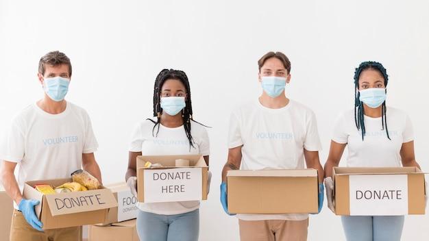 Persone di vista frontale che preparano pacchetti di donazioni Foto Gratuite