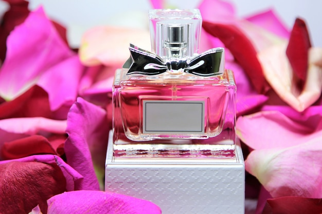Front view perfume bottle on box with pink rose petals Free Photo