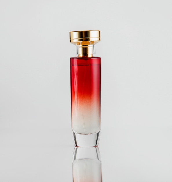Front view perfume bottle glass model of red color with a gold plastic cover Free Photo