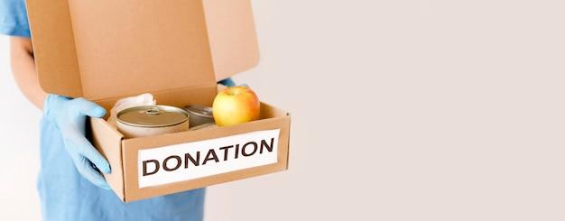 Vista frontale della scatola della tenuta della persona di donazione dell'alimento con lo spazio della copia Foto Gratuite