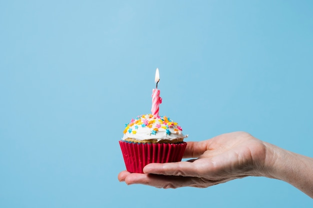Front view person holding cupcake with lit candle Free Photo