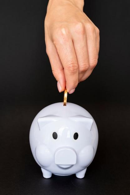Persona di vista frontale che mette una moneta in un salvadanaio Foto Gratuite