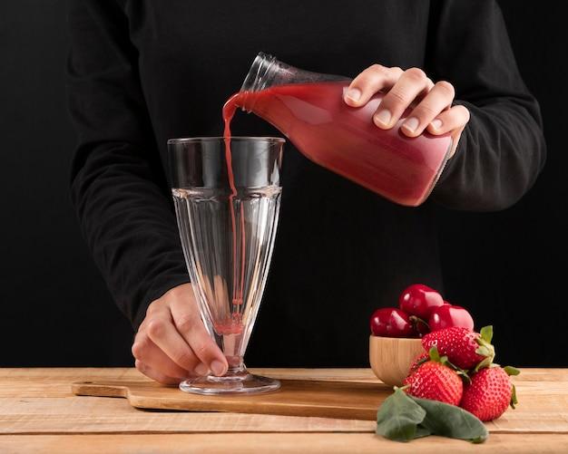 Frullato di versamento della persona di vista frontale in vetro vicino ai frutti rossi Foto Gratuite