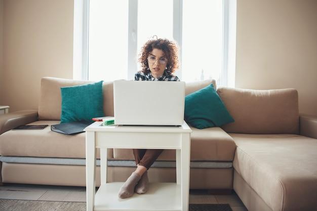 Фотография вид спереди женщины с вьющимися волосами, проводящей онлайн-встречу за ноутбуком, сидя на диване Premium Фотографии
