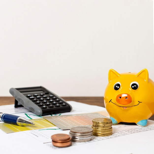 Front view of piggy bank and piles of coins Free Photo