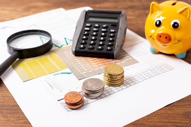 Front view of piggy bank and stationery items Free Photo