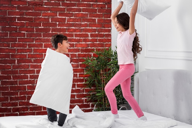 Front view pillow fights between siblings Free Photo