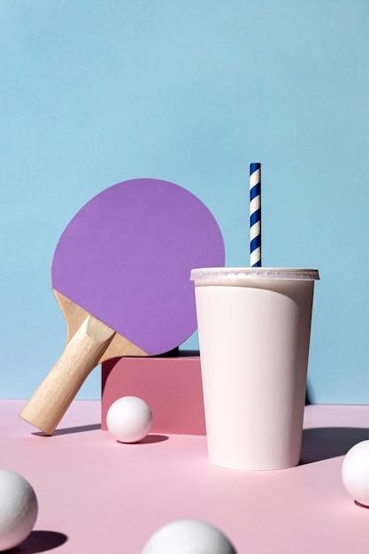 Vista frontale di palline da ping pong e paddle e bicchiere di carta Foto Gratuite