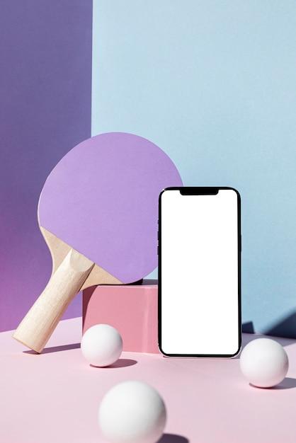 Vista frontale di palline da ping pong e pagaia con smartphone Foto Gratuite