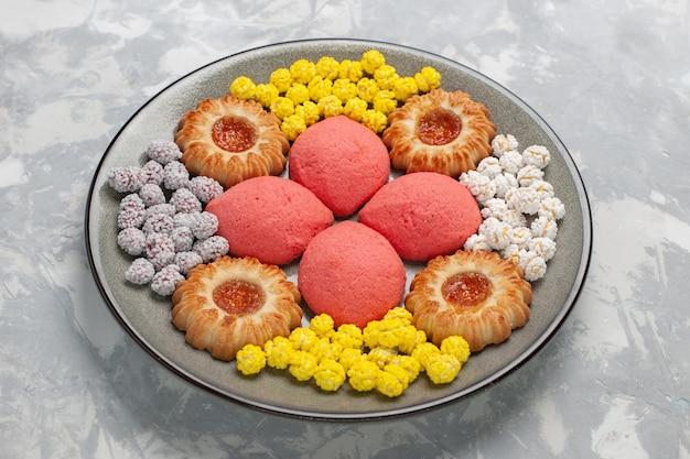 白い表面のプレートの内側にキャンディーとクッキーの正面図ピンクのケーキ 無料写真