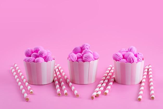 Una vista frontale rosa, biscotti deliziosi e gustosi insieme a caramelle in stick sul rosa, zucchero candito biscotto biscotto Foto Gratuite