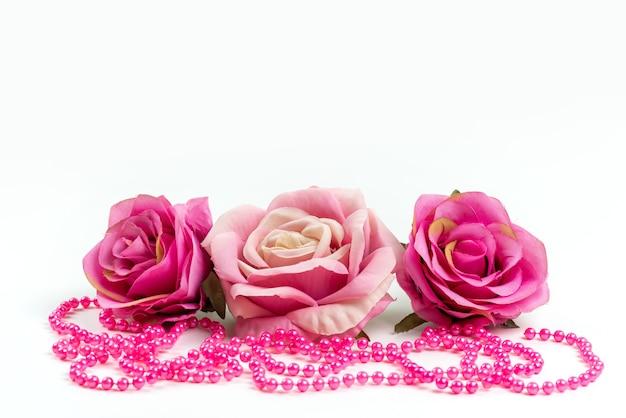 Una vista frontale rose rosa con collana rosa sullo scrittorio bianco Foto Gratuite