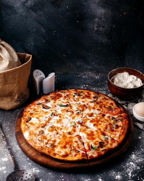 茶色の木製の丸い机と灰色の床に赤いトマトとチーズの正面ピザ 無料写真