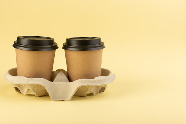 A front view plastic coffee cups delivery coffee pair on the yellow wall Free Photo