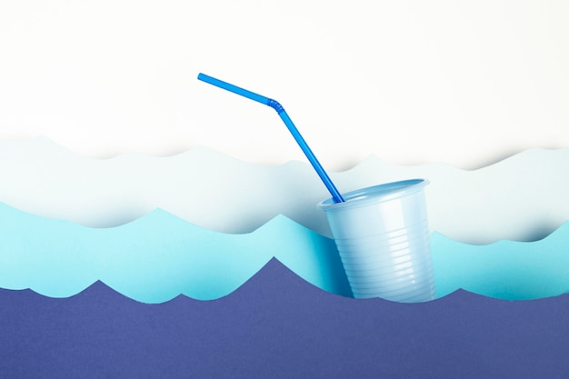 Front view of plastic cup with straw and paper waves Free Photo