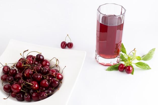 Тарелка переднего вида с вишней кислой и мягкой вместе с листьями вишневого сока на белом Бесплатные Фотографии