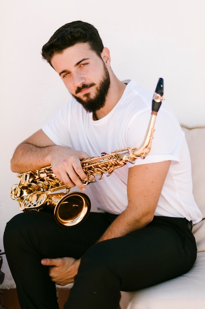 Front view portrait of man posing with sax Free Photo