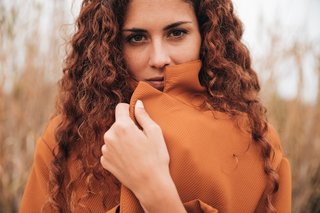 Front view portrait of a woman in trench coat Free Photo