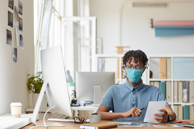 Front view portrait of young african-american photographer wearing mask while reviewing pictures sitting at desk in home studio, copy space Premium Photo