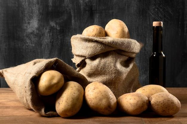 Vista frontale delle patate nel sacco di iuta con bottiglia di olio Foto Gratuite