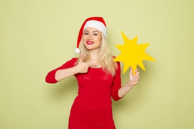 녹색 벽 크리스마스 감정 눈 새해 색상 휴일에 큰 노란색 그림을 들고 전면보기 예쁜 여성 무료 사진