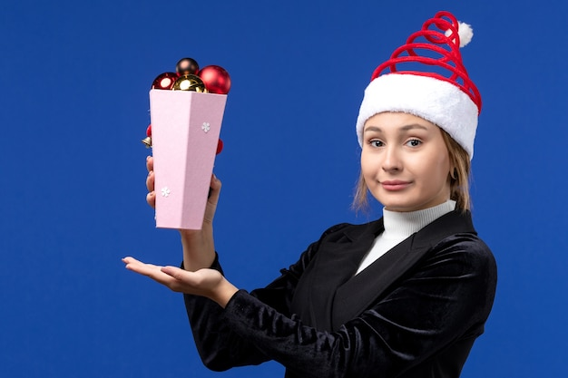 Front view pretty female holding plastic tree toys on a blue wall blue new year holiday Free Photo