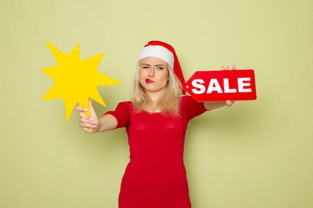 녹색 벽 눈 감정 크리스마스 새해 색상에 판매 쓰기와 큰 노란색 그림을 들고 전면보기 예쁜 여성 무료 사진