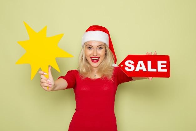 전면보기 예쁜 여성 판매 쓰기 및 녹색 벽 눈 감정 휴일 크리스마스 새해 색상에 큰 노란색 그림을 들고 무료 사진