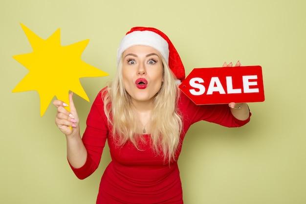 正面図きれいな女性が販売の執筆と緑の壁に大きな黄色の図を保持雪感情休日クリスマス新年の色 無料写真