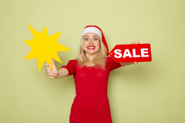 正面図きれいな女性が販売の書き込みと緑の壁に大きな黄色の図を保持雪感情休日新年の色 無料写真