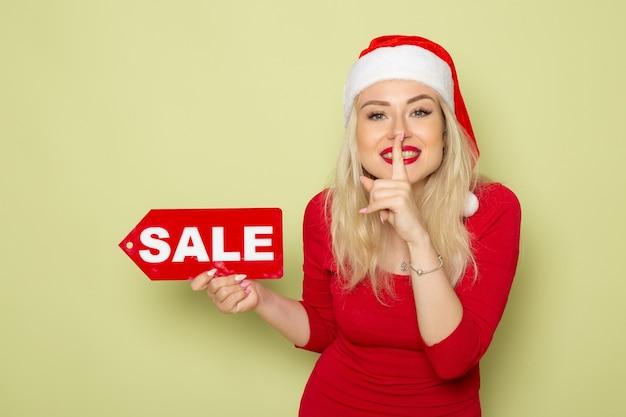 正面図きれいな女性が販売を保持している緑の壁の感情の休日のクリスマス新年の色に書き込みます 無料写真