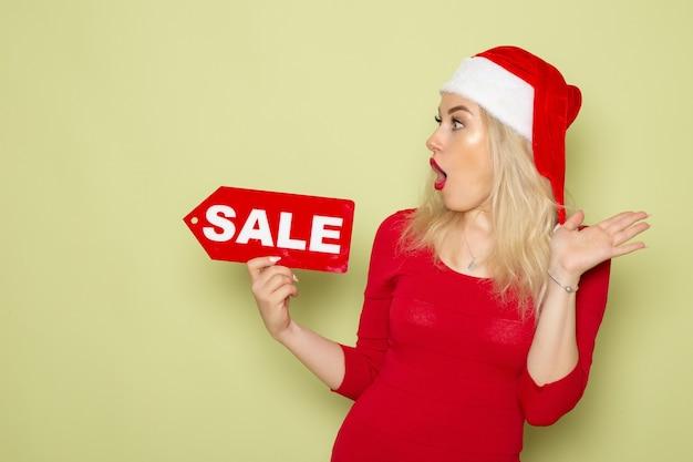 正面図きれいな女性が販売を保持している緑の壁に書き込み雪感情休日クリスマス新年色 無料写真