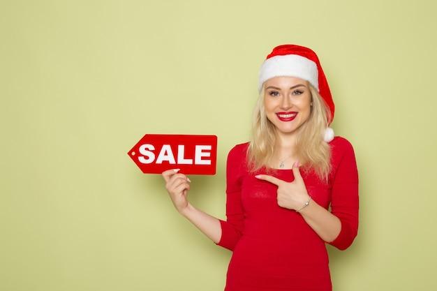 正面図きれいな女性が販売を保持している緑の壁に書き込み雪感情休日クリスマス新年の色 無料写真