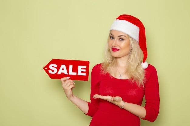 正面図きれいな女性が緑の壁に販売を書いている雪の感情の休日クリスマス新年 無料写真