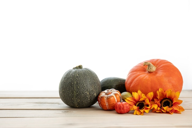 Front view pumpkins on wooden table wih sunflowers Free Photo