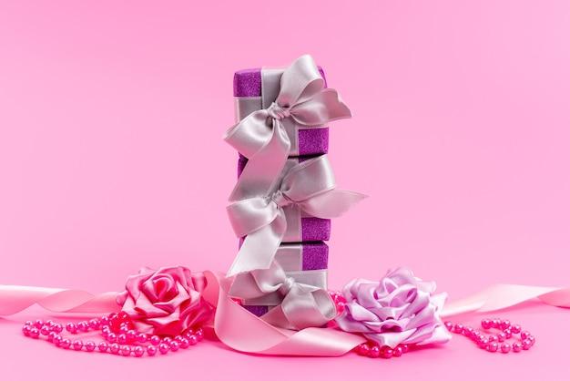 Una vista frontale viola scatole regalo con fiocchi e fiori sulla scrivania rosa Foto Gratuite