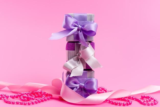 Una vista frontale viola scatole regalo con fiocchi in rosa Foto Gratuite